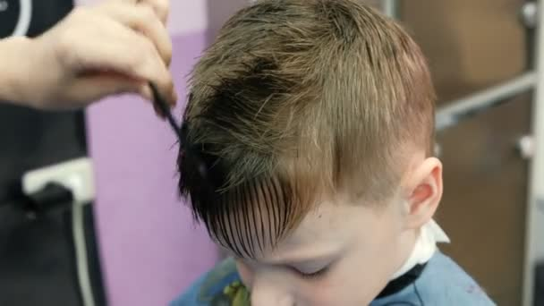 Barber Combs Sprays With Water And Cutting Blond Short Boys Hair With Scissors Side View