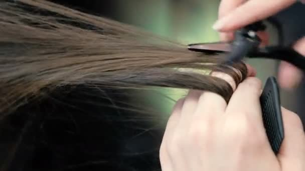 Barbers hands cutting long brunette hair hot scissors. Closeup.
