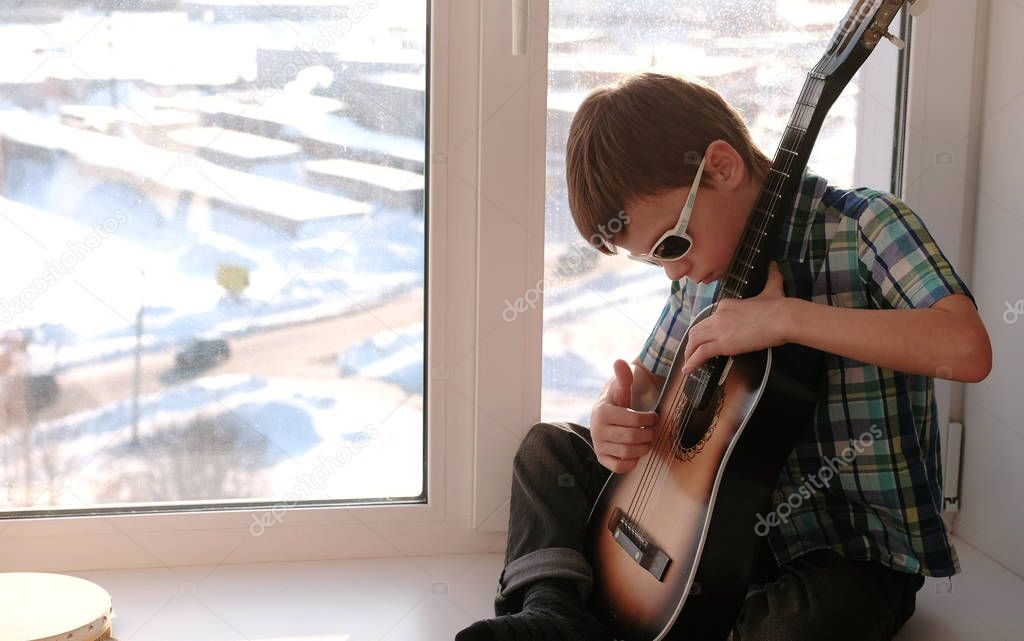 Playing a musical instrument. Boy in sunglasses learns to play the guitar, sitting on the windowsill.
