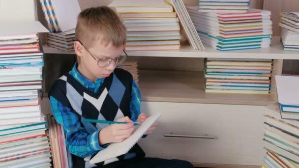 Sedm rok starý chlapec s brýlemi kreslí něco v sketchbook sedí mezi knihami.