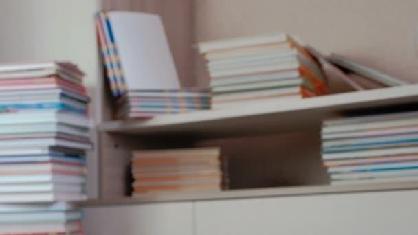 Hromada knih na podlaze a na skříni regály. Rozostření.