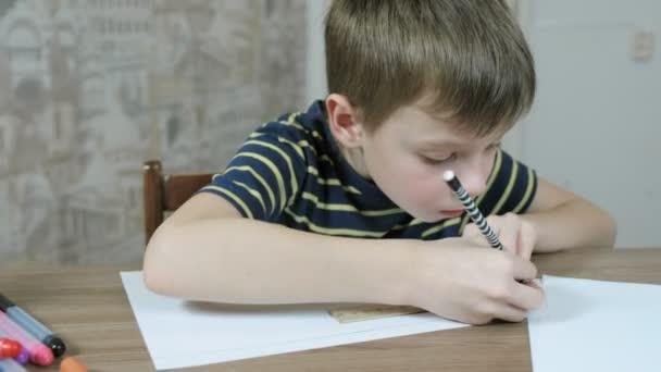 Fiú a csíkos póló 7 éves vonalakat rajzol, még a könyv egy vonalzó és egy ceruza