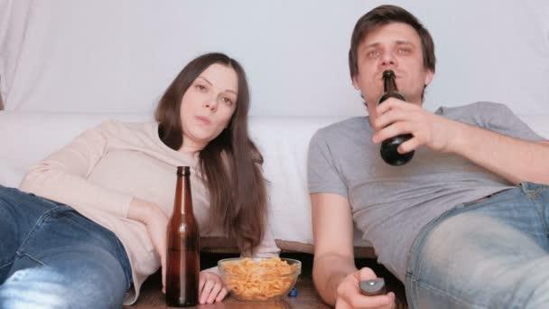Dva mladý muž a žena jíst chipsy popíjeli pivo a sledování televize, přepínání kanálu. Mluvení a usmívá se