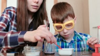 Chemistry experiments at home. Mom and son make a chemical reaction with the release of gas in the test tube.