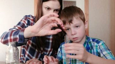 Chemistry experiments at home. Woman puts the red paint in a test tube with water in the hands of the boy.