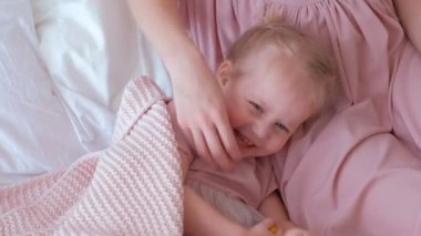 Little charming blond girl plays hide and seek with her mom in pink dress laying on bed.