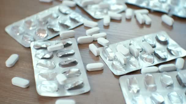 Closeup mans rukou bere bílé pilulky. Prášky a puchýře prášků. Záchvat, otravy, lékařství