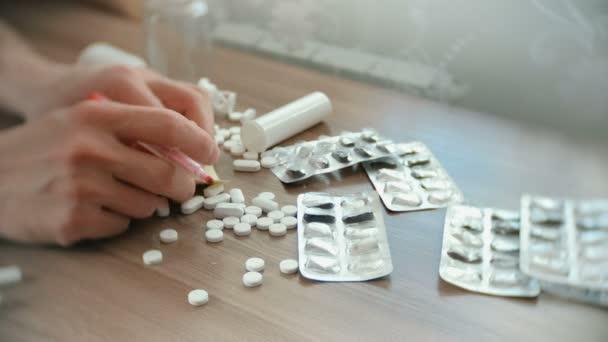 Pánské ruce sklouznout stůl s bílými prášky, puchýře a tablety