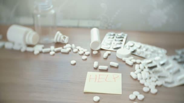 Nápis na štítku help - mezi rozptýlené prášky na stole. sebevražda