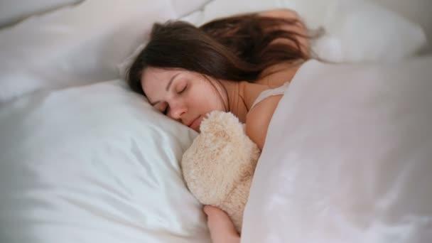 Fiatal nő alszik a játék medve.
