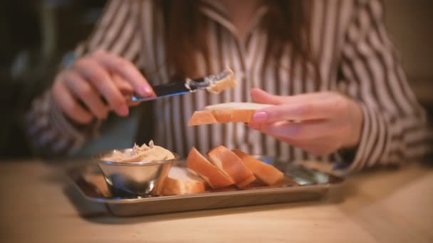 Bruneta Mladá krásná žena nátěry paštiku na kousek chleba v kavárně. Detail Zenske ruce s nožem
