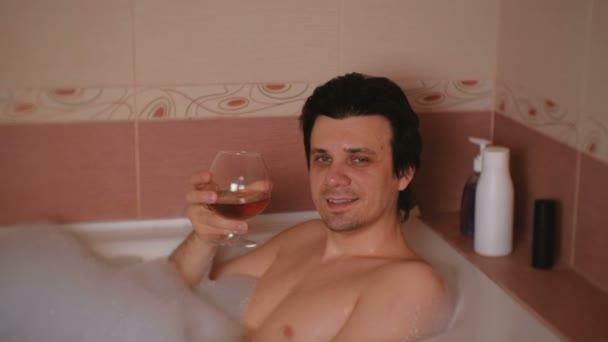 Mladík bere koupel s pěnou a do pití whisky. S úsměvem a při pohledu na fotoaparát.