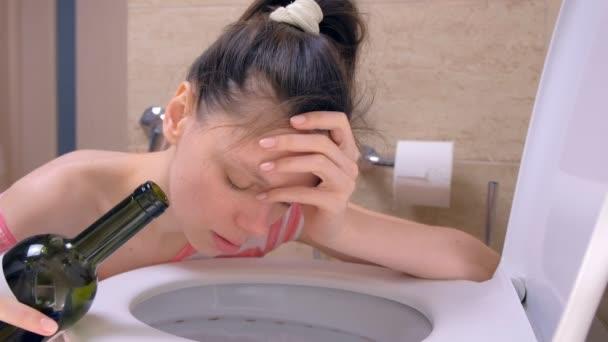Betrunkene Frau erbricht in Toilette sitzend auf dem Boden mit Weinflasche in der Hand zu Hause, Morgen Kater, Seitenansicht.