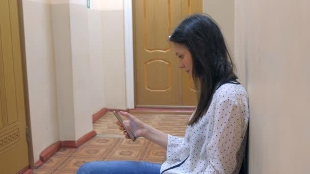 junge Frau wartet auf Vorstellungsgespräch am Telefon in der Nähe der Tür.