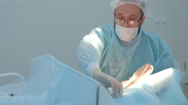 Chirurg muž stehy kotník na noze během operace s self-absorbovatelné nitě.