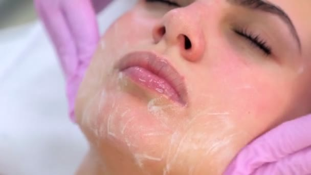 Cosmetologo in guanti lava i clienti viso, collo e petto donna con gel.