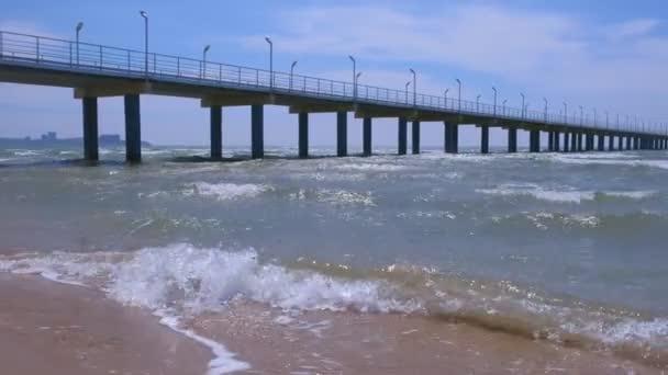 Pohled na mořskou písečnou pláž s vlnami přímořských měst a hor za slunečného dne.
