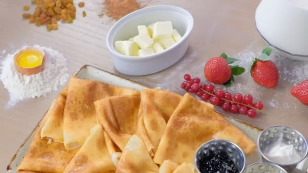 Ruské tradiční palačinky, Bliny servírovaná s džemy, zakysanou smetanou a jahody na desce. Detail boční pohled.