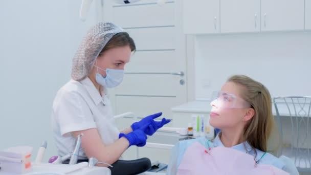 Zubař mluví s pacientkou na klinologii preventivní zkoušky.