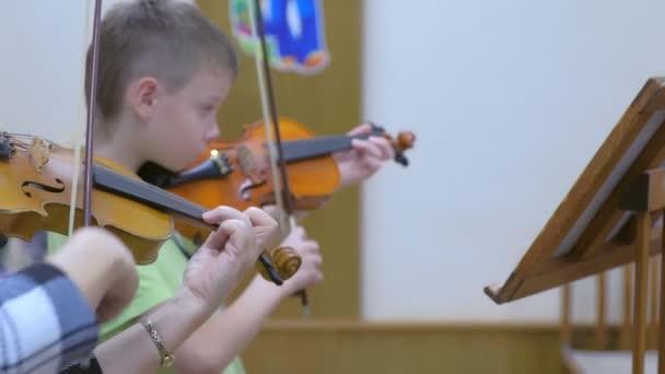 Gyermek fiú diák hegedülni tanár zeneóra a zenei iskolában.
