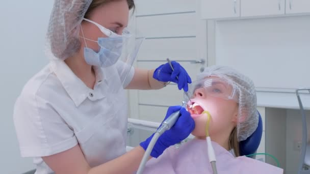 Dentist cleaning brushing and polishing womans teeth uses drill in dentistry.