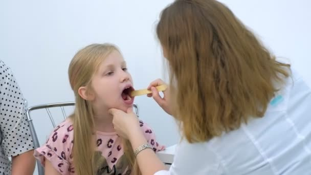 Pediatrician woman looking child girl sore throat using spatula and lantern.