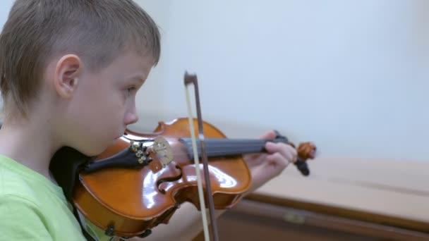 Kisgyerek hegedülni gyakorol a zeneórán az iskolában..