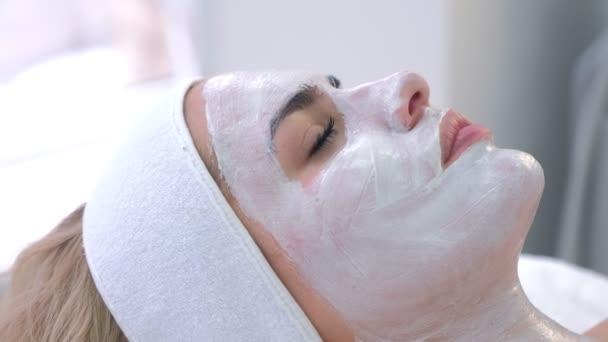 Frauenporträt im Wellness-Salon mit weißer Maske im Gesicht, Seitenansicht.