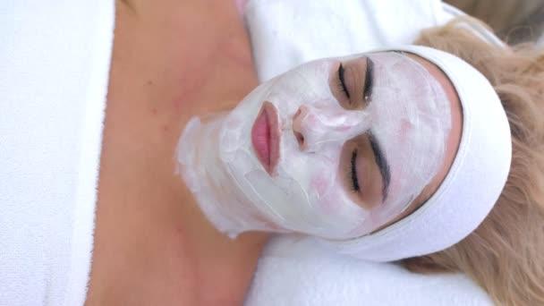 Frauenporträt im Wellness-Salon mit weißer Maske im Gesicht, Draufsicht.