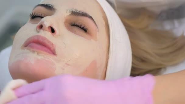 Kosmetikerin in Handschuhen wischt Hautpflegemaske aus Frauengesicht, Nahaufnahme Porträt.