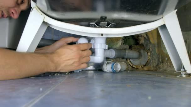 Instalatér opravy výměna trubek s novými pod vanou v koupelně.