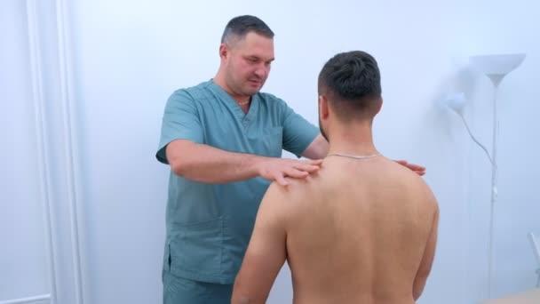 Doktor chiropraktik léčí pacienty na klinice na rehabilitační terapii.