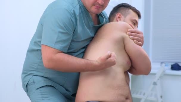 Lékař chiropraktik léčí pacienta na klinice na rehabilitační terapii.