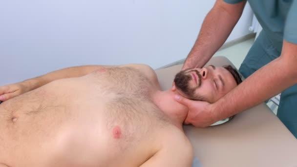 Chiropraktik ostře otáčí krk pacientů na klinice na rehabilitační terapii.