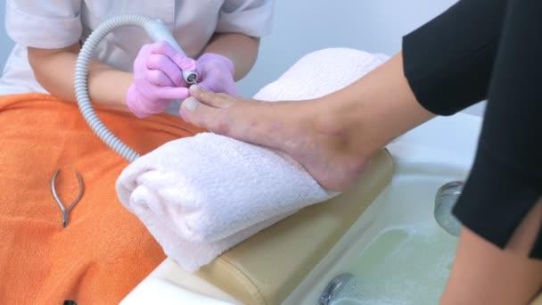 Fußpflegerin entfernt Nagelhaut aus Zehen von Kunden mit elektrischem Nagelmaschine.