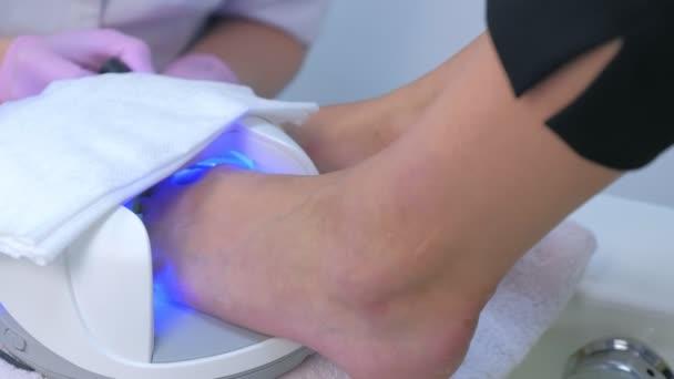 Frau trocknet Schellack auf Zehen in UV-Lampe im Schönheitssalon, Nahaufnahme Ansicht.