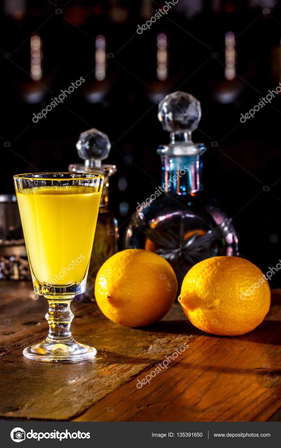 vaso de Limoncello está sobre la mesa en el cuarto oscuro. En el bac ...