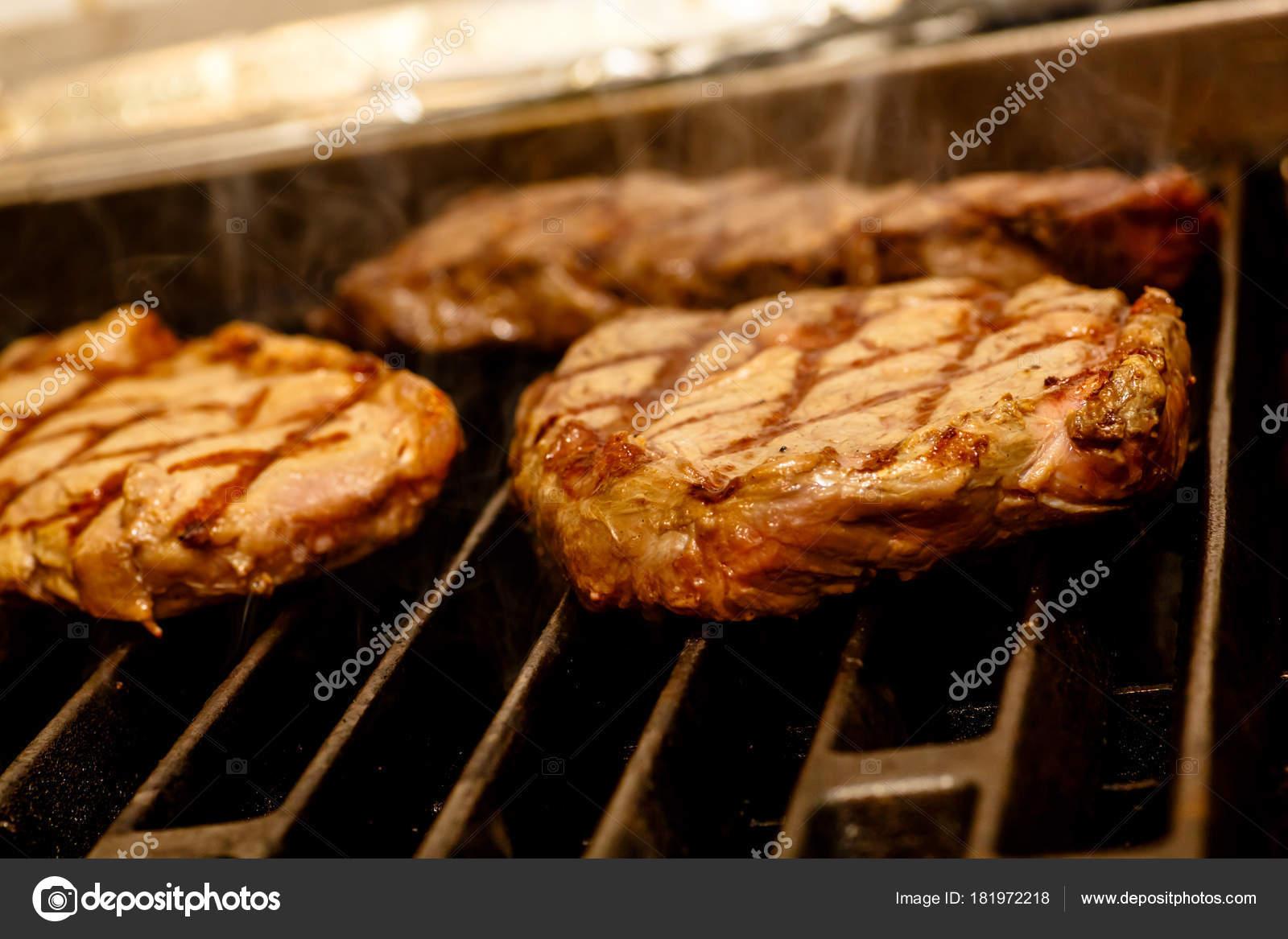 Повар готовит стейки