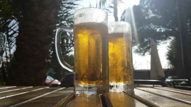 Kouřící hrnek studeného piva na stole letní kavárny v jižním městě.
