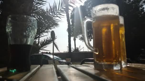 Egy gőzölgő korsó hideg sör egy déli városi kávézó asztalán..