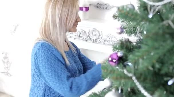 Dame schmücken den Weihnachtsbaum lächelnd