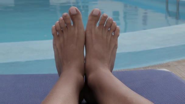 Nohy s nalakovanými nehty leží na palubě vedle bazénu