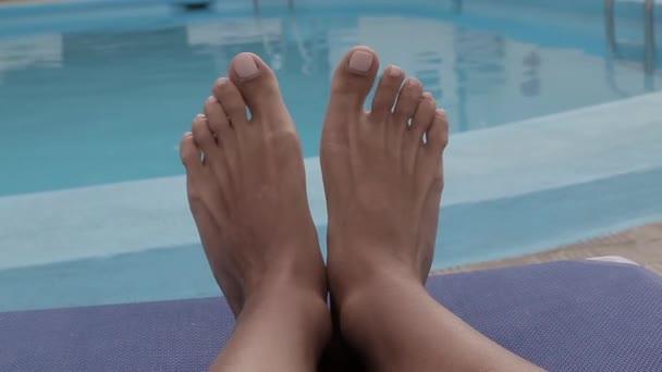 Nohy s nalakovanými nehty se přesouvají na lehátko u bazénu