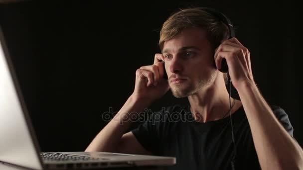uomo indossare cuffie, brano musicale impostata sul computer portatile