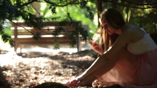 Krásná žena se dotýká její dlouhé vlasy v paprscích slunce teplé léto venku v zahradě