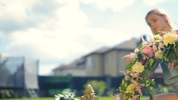 Corsi per bambini attività extrascolastiche floristik ricevimento decorazioni - biondo di modello femminile grazioso sorridente composizione floreale che fa ragazza dai fiori sullerba verde smeraldo allaperto
