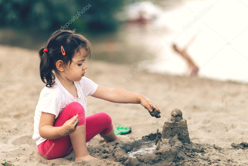 Cute little girl playing on beach