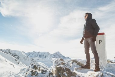 Portrait of a winter-dressed man in full growth on top of snowy mountains