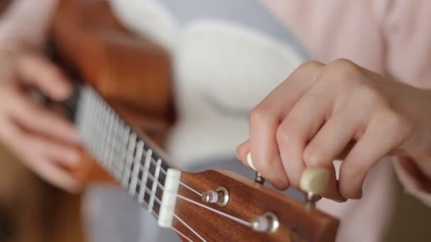 Holky rukou otočí ukulele kolíčky na tuning to