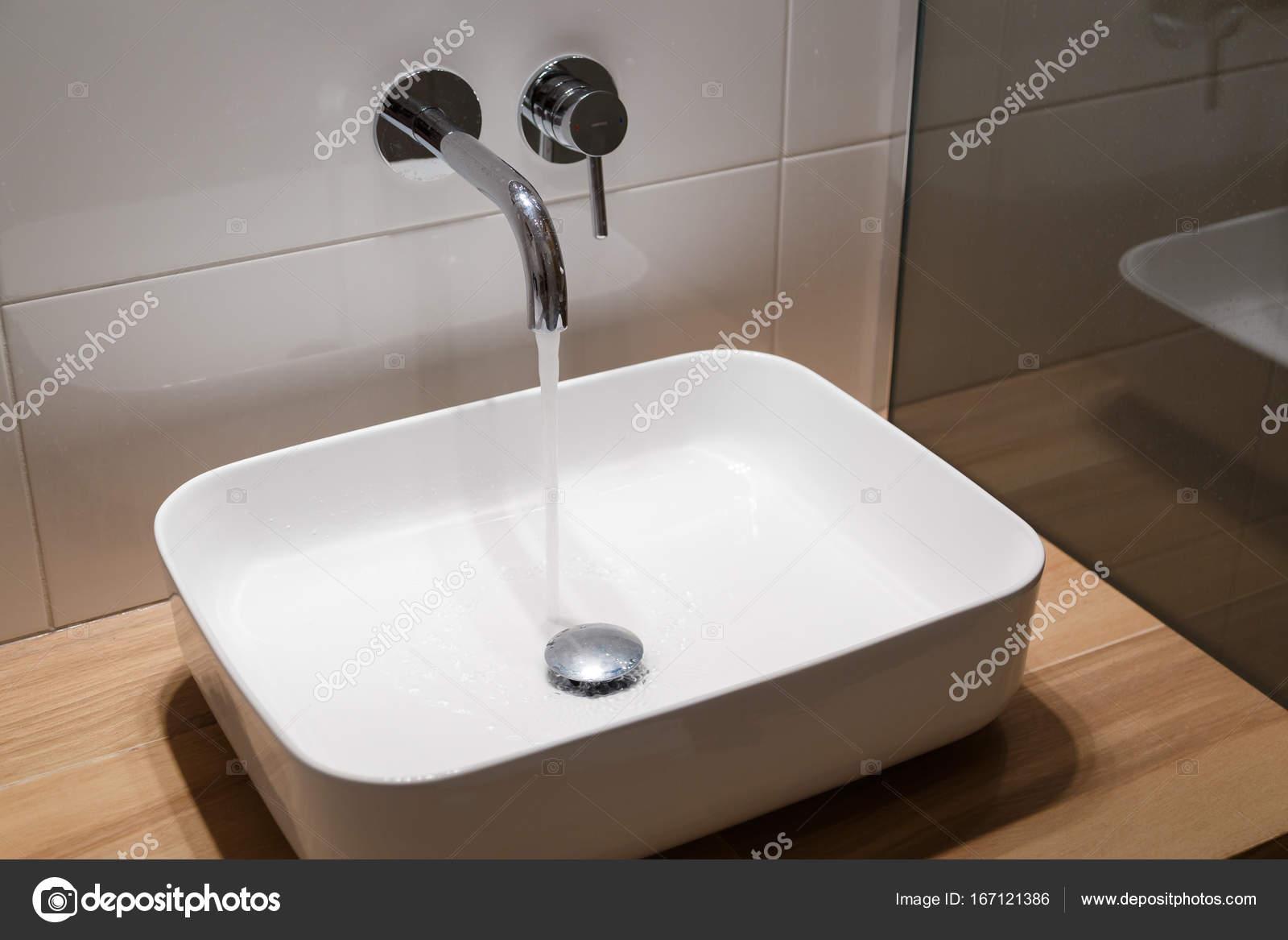 Close up van wastafel en kraan op houten plank in witte badkamer ...